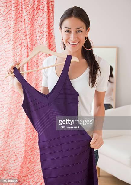 Hispanic woman holding dress at store