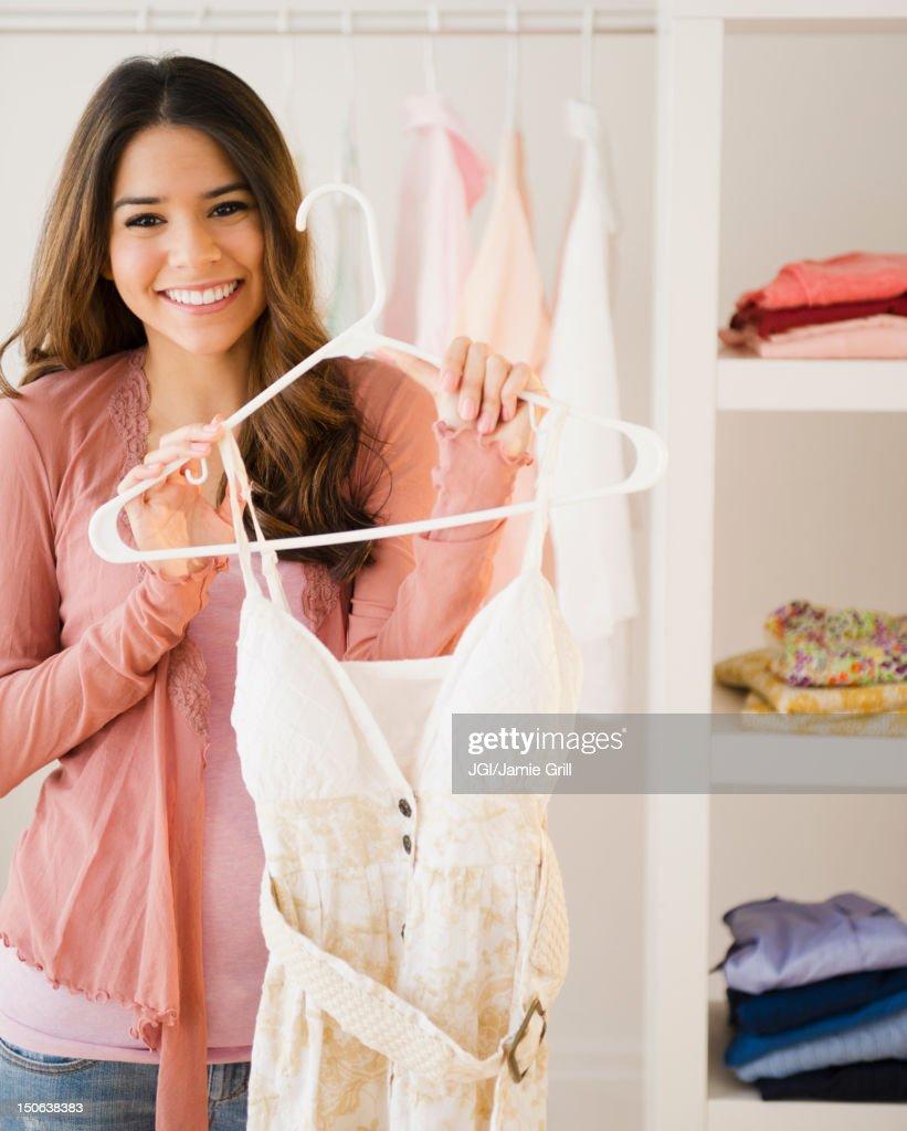Hispanic woman holding dress on hanger