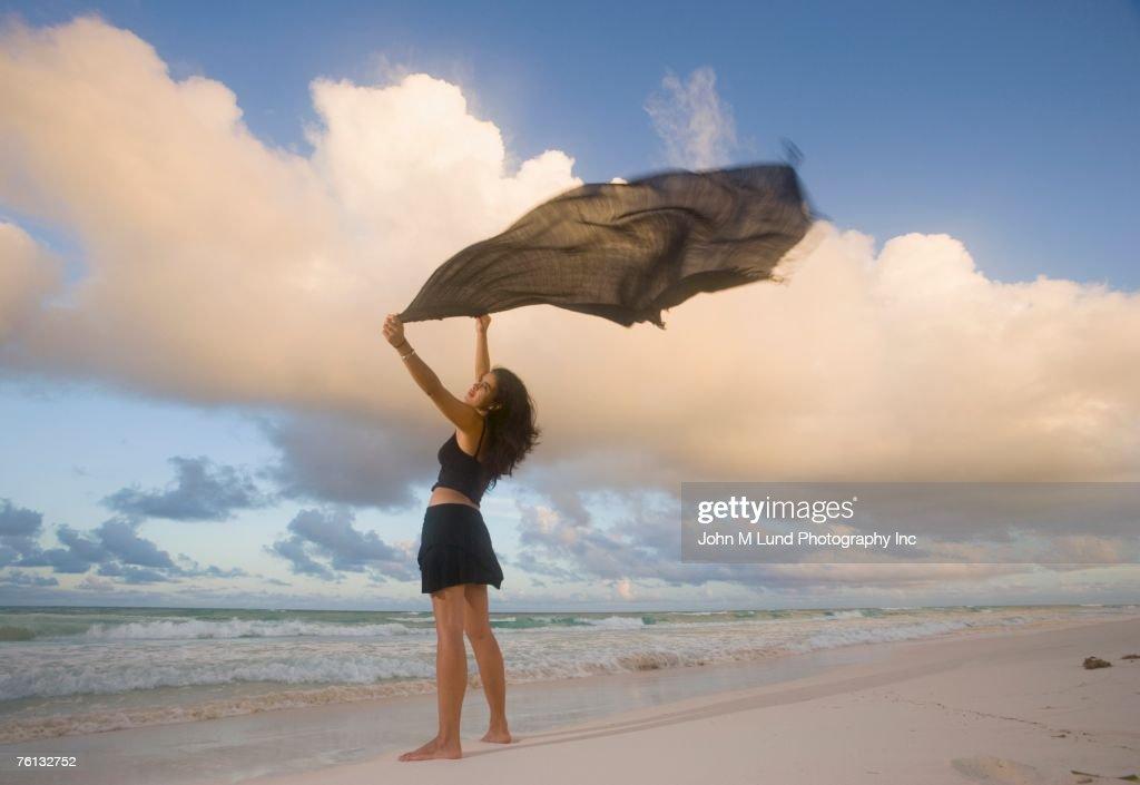 Hispanic woman holding flowing scarf on beach : Stock Photo