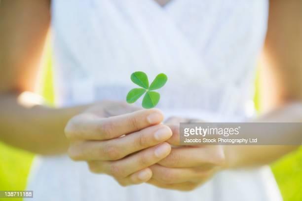 Hispanic woman holding four-leaf clover