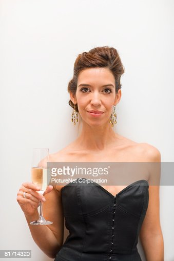 Hispanic woman holding glass of champagne