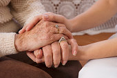 Hispanic woman holding hands with senior woman