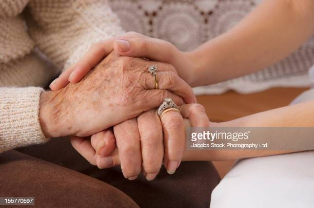 Hispanic woman holding hands with senior woman