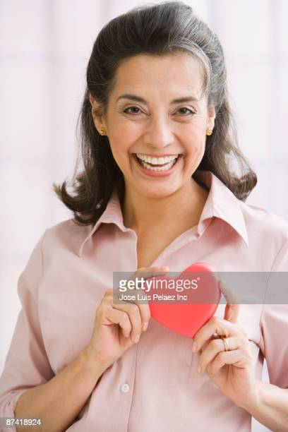 Hispanic woman holding heart-shaped object