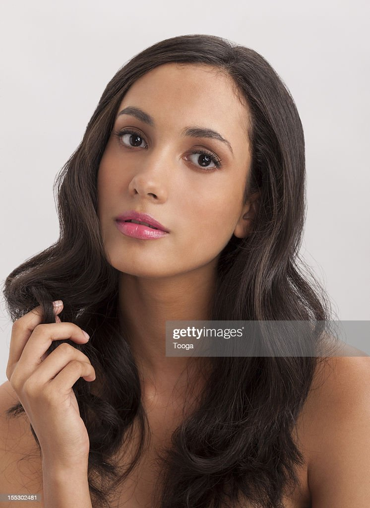 Hispanic woman holding lock of hair : Stock Photo