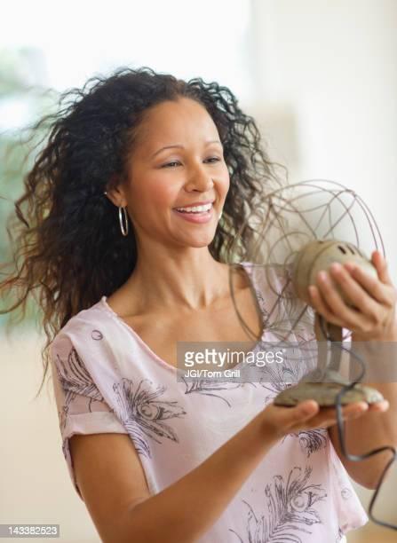 Hispanic woman holding old-fashioned fan