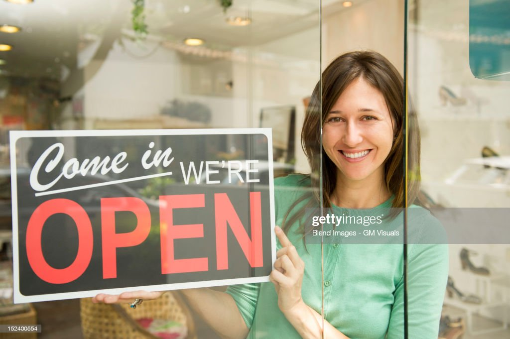 Hispanic woman holding open sign in shoe store : Stock Photo