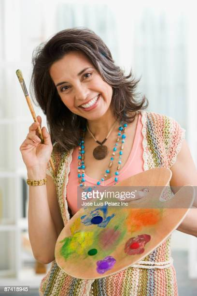 Hispanic woman holding paintbrush and color pallet