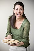 Hispanic woman holding plate of cookies and smiling
