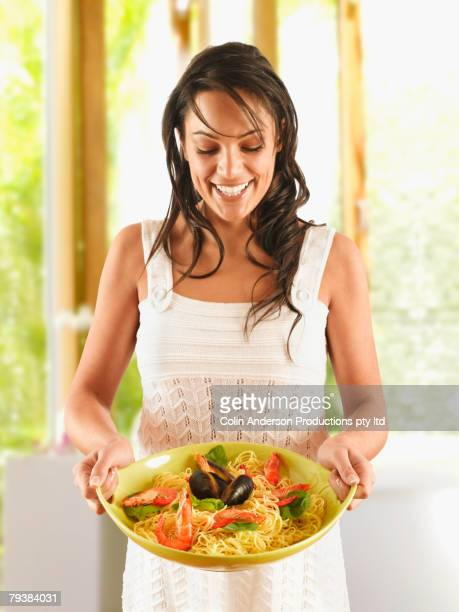 Hispanic woman holding plate of pasta