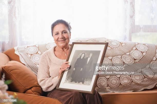 Hispanic woman holding portrait of parents
