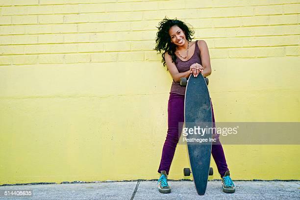 Hispanic woman holding skateboard on city street