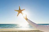 Hispanic woman holding starfish at beach