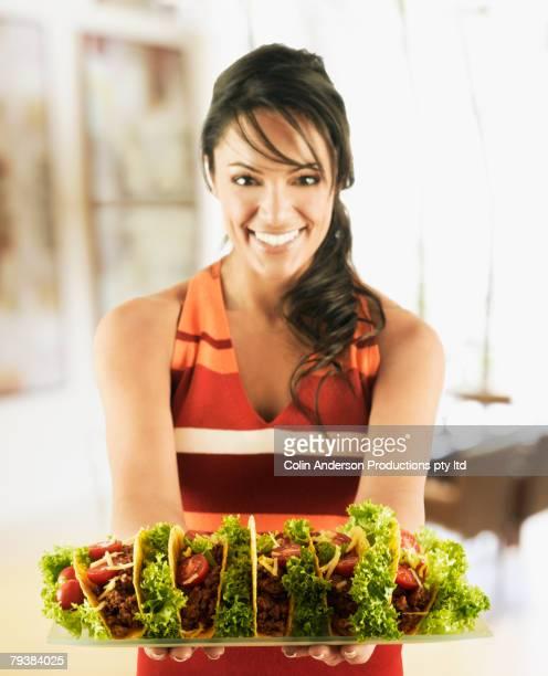 Hispanic woman holding tray of tacos
