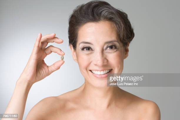 Hispanic woman holding vitamin