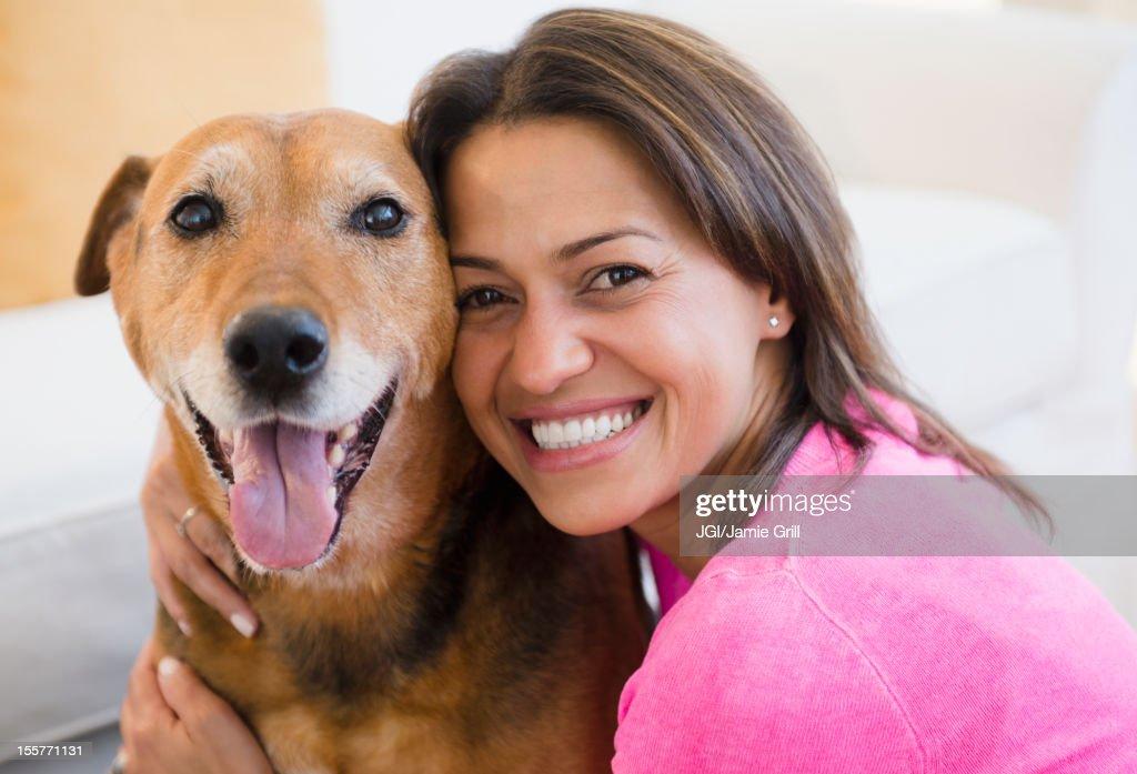 Hispanic woman hugging dog : Stock Photo