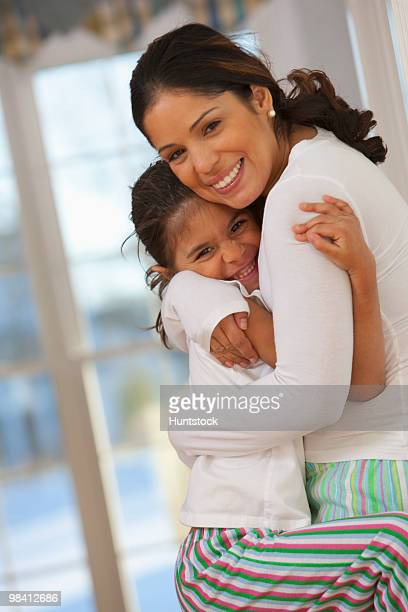 Hispanic woman hugging her daughter