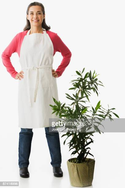 Hispanic woman in apron with house plant