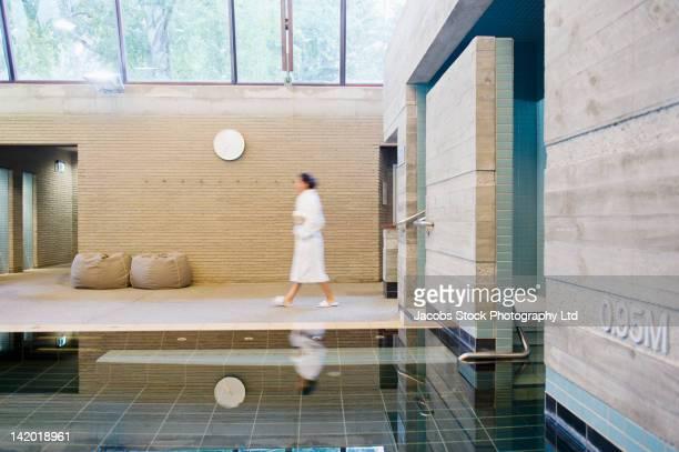 Hispanic woman in bathrobe walking in spa