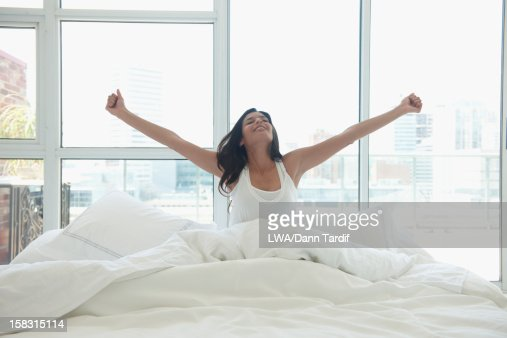 Hispanic woman in bed with arms outstretched