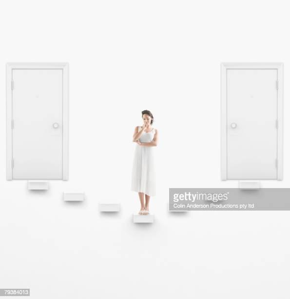 Hispanic woman in between two doors