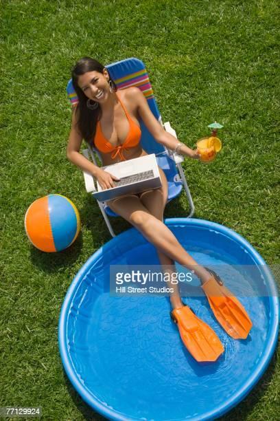 Hispanic woman in bikini next to kiddie pool