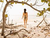 Hispanic woman in bikini standing on beach