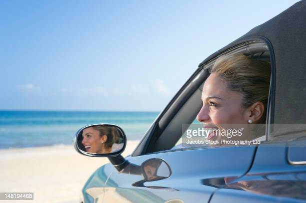 Hispanic woman in car enjoying the beach