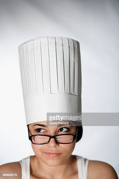 Hispanic woman in chef's hat and eyeglasses