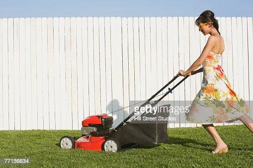 Hispanic woman in dress pushing lawn mower