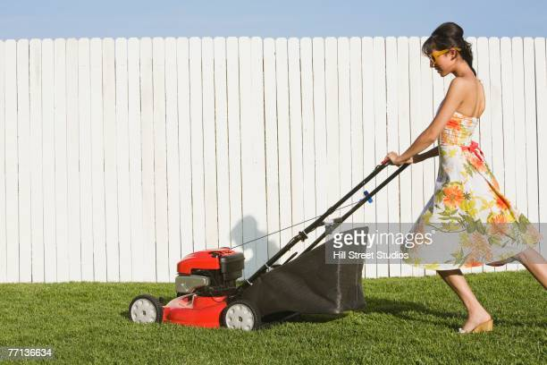 Hispanic woman in dress pushing lawn mower