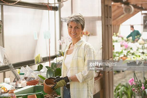 Hispanic woman in greenhouse potting flowers