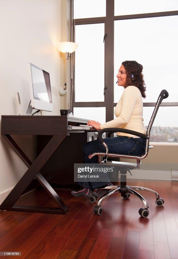 Hispanic woman in headset working on computer