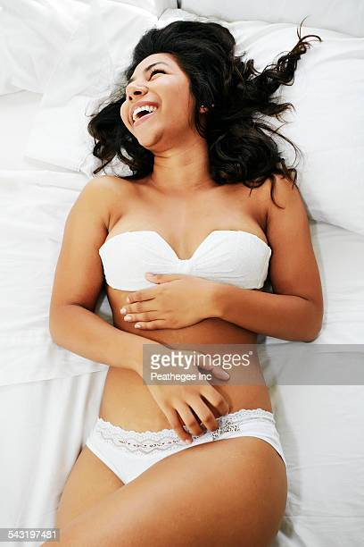 Hispanic woman in lingerie laughing on bed