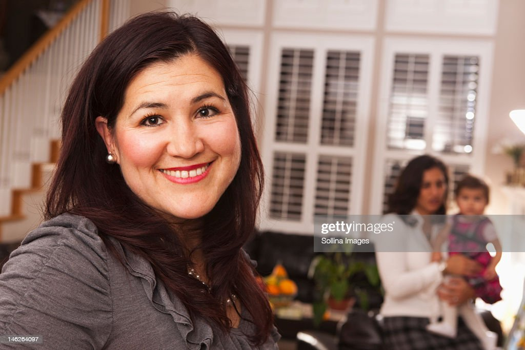 Hispanic woman in living room with family