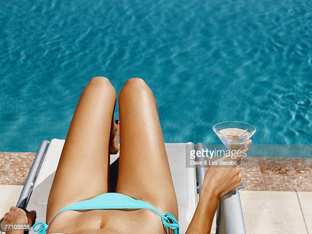 Hispanic woman in lounge chair next to swimming pool