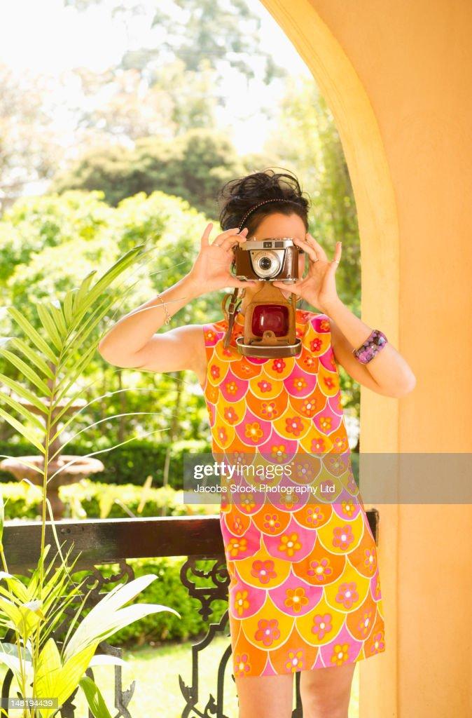 Hispanic woman in nostalgic dress using retro camera : Stock Photo