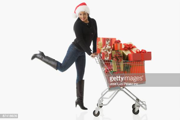 Hispanic woman in santa hat with Christmas gifts
