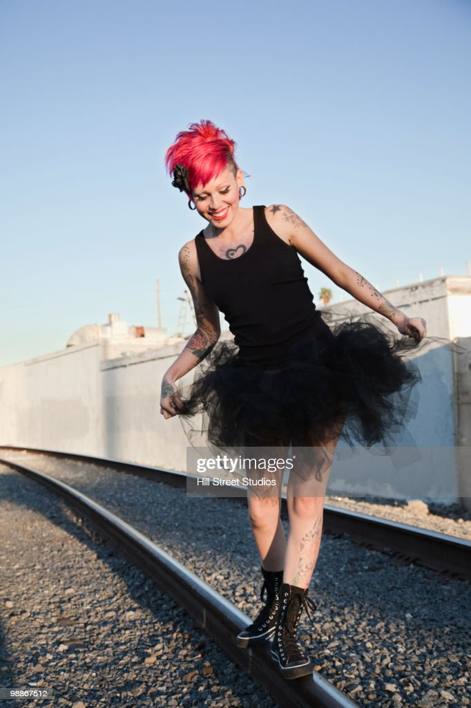 Hispanic woman in tutu on railroad tracks