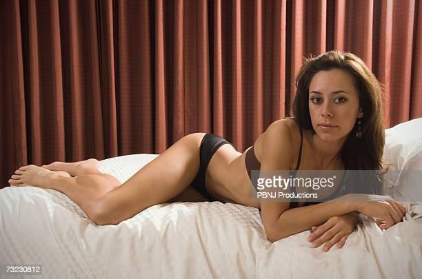 Hispanic woman in underwear laying on bed