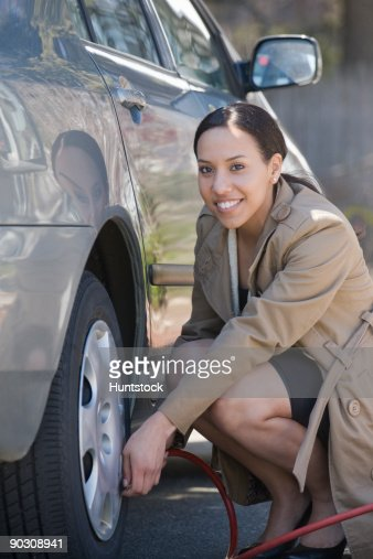Hispanic woman inflating a tire of a car : Photo