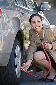 Hispanic woman inflating a tire of a car