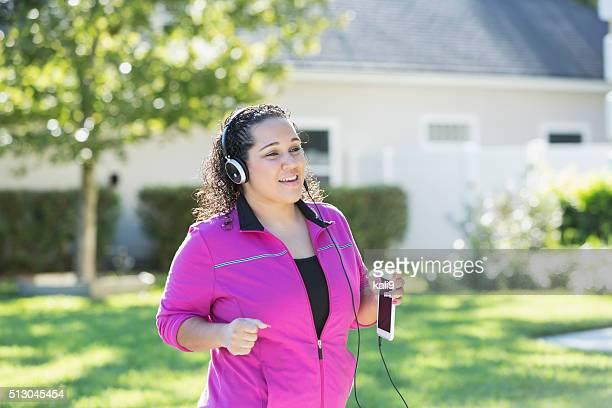 Ispanica donna fare jogging e ascoltare musica sul cellulare