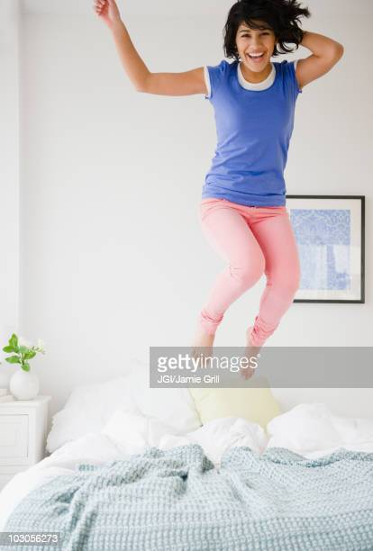 Hispanic woman jumping on bed