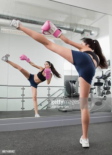 Hispanic woman kick boxing in health club