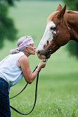 Hispanic woman kissing horse