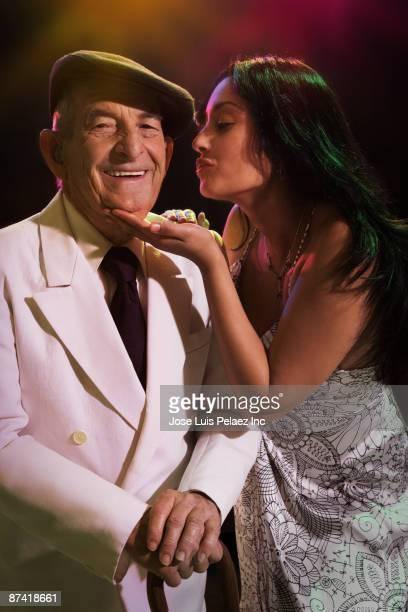 Hispanic woman kissing senior man in nightclub