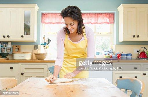 Hispanic woman kneading dough on kitchen table