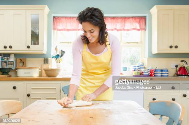 Hispanic woman kneading dough on kitchen table