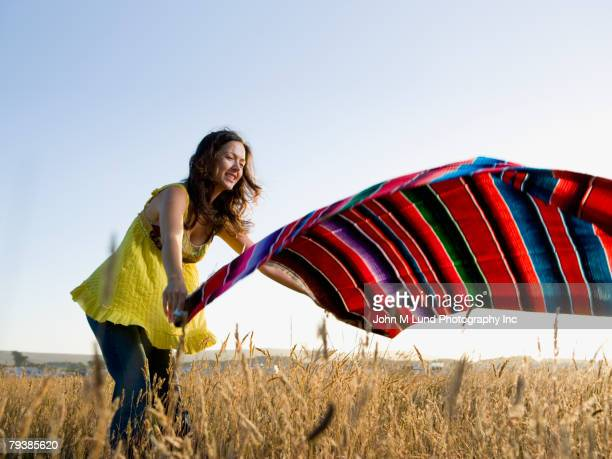 Hispanic woman laying blanket in field